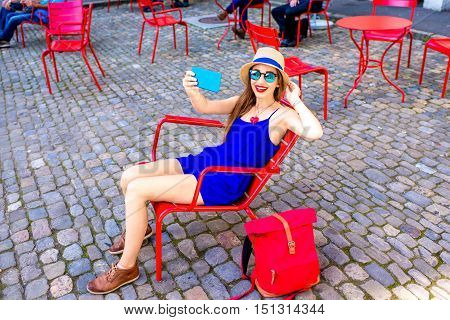 Young female tourist making selfie photo sitting on the red public chairs on Munster square in the old town of Bern city in Switzerland