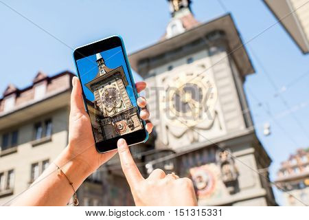 Photographing with phone a famous clock tower in Bern city in Switzerland
