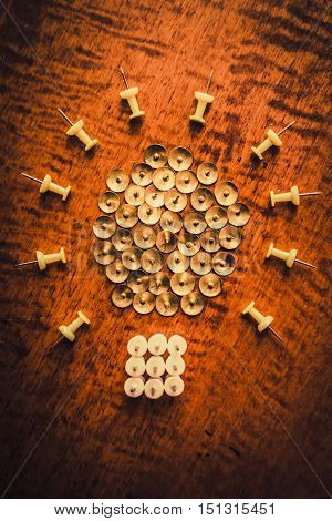 Light beaming on brass and plastic material pushpins arranged on wooden office desk. Corporate lightbulb icon