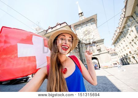 Young female tourist making selfie photo in front of the famous clock tower in the center of the old town of Bern city in Switzerland. Having a great vacations in Switzerland
