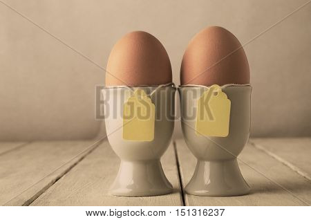 A pair of brown eggs in eggcups with price tag style labels on string. Old white wooden planked table. Hues adjusted for retro or vintage appearance.
