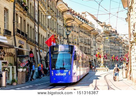 Bern, Switzerland - June 24, 2016: Street view on Kramgasse with modern blue tram in the old town of Bern city. Kramgasse is a popular shopping street and medieval city centre of Bern, Switzerland