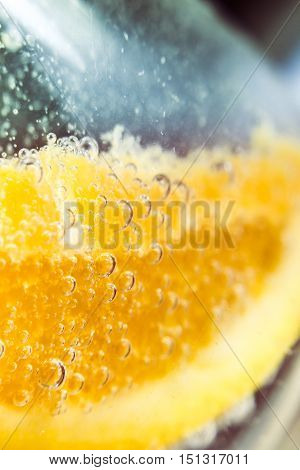 Macro detail on a orange slice in clear bubbly cocktail glass. Nightclub beverages