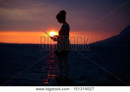 pretty sexy female silhouette of woman or girl with computer or laptop outdoor over dramatic dark sky with clouds and sea or ocean water horizon on evening or twilight on natural sunset background