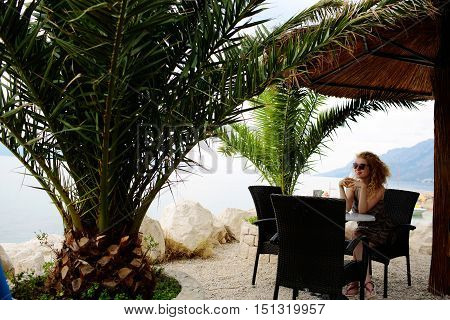 Pretty girl or woman with curly blond hair drinks cocktail in sea beach cafe or bar under sun umbrella and palms on beautiful seascape