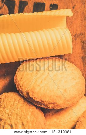 Close up of fresh baked cookies with piece of butter lying on wooden bakehouse bench