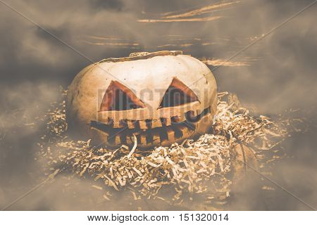 Creepy jack o lantern halloween pumpkin on countryside barn straw shouded in mistry terror