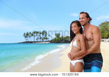 Happy attractive interracial couple relaxing standing on perfect beach with turquoise ocean water for summer vacation travel. Multiracial man and woman in their 20s hugging together.