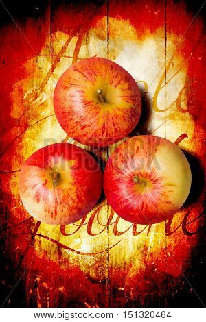 Top down view on three raw whole honeycrisp type apples on wood surface with cursive text. Apple barn artwork