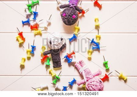 Bright and colorful halloween concept on three scary monster voodoo dolls amongst colourful pins. All hallows eve background