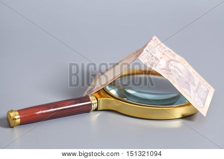 Indian Currency Rupee Notes with magnifying glass on gray