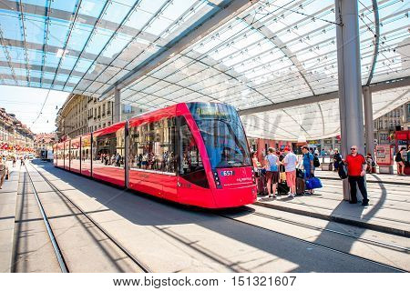 Bern, Switzerland - June 24, 2016: Modern tram station with red tram and people on Bubenberg place in the old town of Bern in Switzerland.