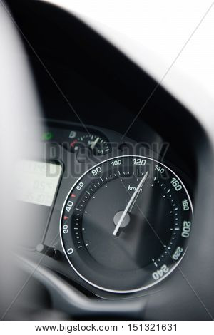 Car speedometer close-up with the needle pointing a high 130 km/mph speed blur effect and blue tone to depict high speed concet and security driving electric car