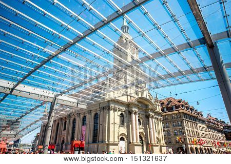 Bern, Switzerland - June 24, 2016: Modern tram station with glass construction and view on Holy Spirit church in Bern city in Switzerland