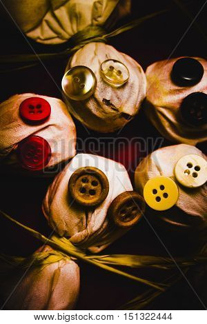 Artistic dark horror lollypop still life art on ghostly sack monsters laying in close proximity with evil button eyes. Little halloween horrors