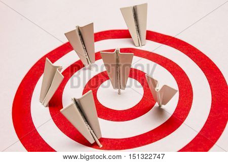 Darts that resemble folded paper airplanes stuck in red and white rings of circular shaped target