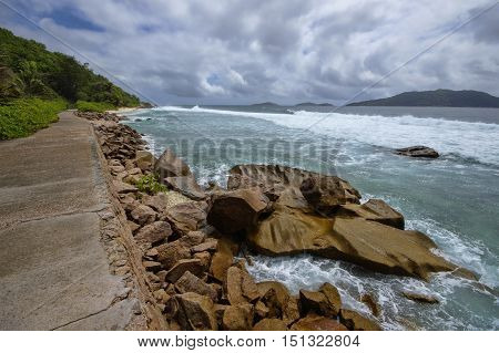 Low tide at the wild east coast of La Digue Seychelles with the only road in the foreground