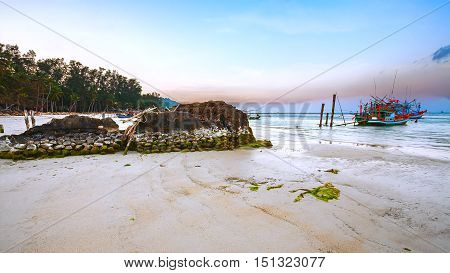 Beautiful sunset on the coast. Fishing wooden boat in the sea and the old stone wall. (Thailand).