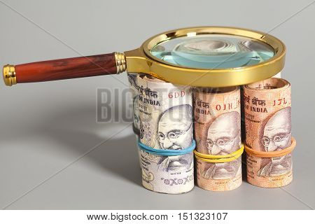 Rolls of Indian Currency Rupee Notes with magnifying glass on gray