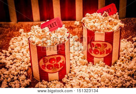 Retro still life photo on two old fashioned pop corn tins with show tickets at ticketing stands. Carnivals and theatre