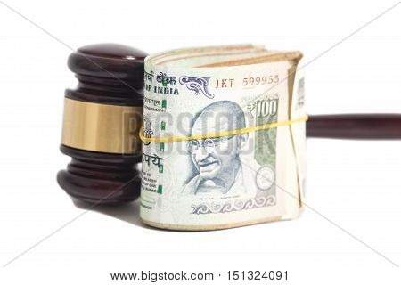 Judge gavel and Indian Currency Rupee bank notes on white background