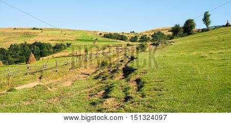 Wooden fence against the summer landscape in the Ukrainian Carpathian Mountains.
