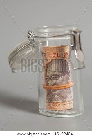 Money Indian Currency Rupee Notes in glass jar on gray background
