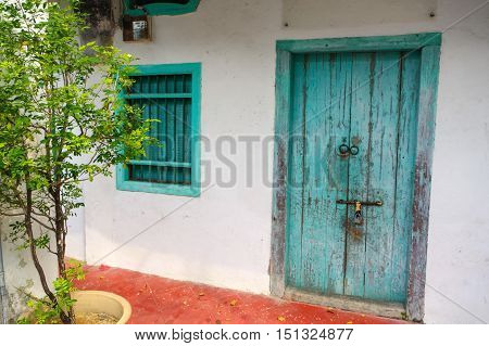 a House in George Town Penang Malaysia. Mediterranean style exterior. Blue wooden doors and window shutters on old painted wall