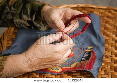 Old Woman Hand Embroiders With A Thread