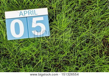 April 5th. Day 5 of month, wooden color calendar on football green grass background. Spring time, empty space for text.