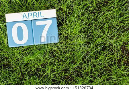 April 7th. Day 7 of month, calendar on football green grass background. Spring time, empty space for text.