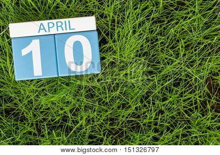 April 10th. Day 10 of month, calendar on football green grass background. Spring time, empty space for text.
