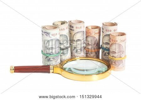 Rolls of Indian Currency Rupee Notes with magnifying glass isolated on white background