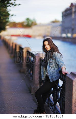 Young pretty long-haired girl with beautiful brown eyes on the waterfront of St. Petersburg at sunset