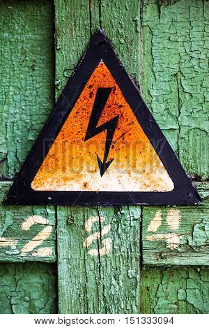 Old rusty warning high voltage sign on cracked green wooden surface