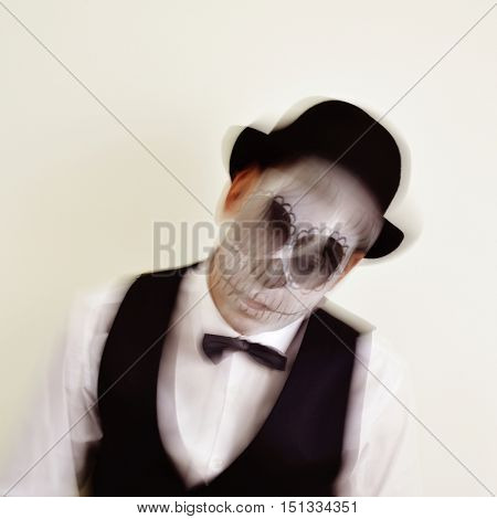 portrait of a man with a mexican calaveras makeup, wearing waistcoat, bow tie and bowler hat, in motion