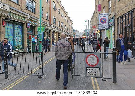 LONDON UNITED KINGDOM - NOVEMBER 24: People Walking at Brick Lane in East London on NOVEMBER 24 2013. Brick Lane is Busy on Sunday in East London United Kingdom.