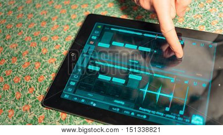 use music app on a tablet. Young man listening to your favorite music on the computer tablet