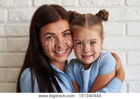 Close-up horizontal portrait of Caucasian young mother and her cute daughter wearing casual light-blue denim outfit while posing at camera