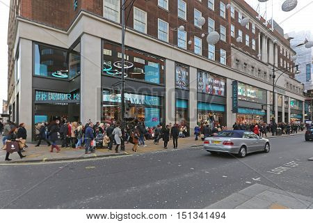 LONDON UNITED KINGDOM - NOVEMBER 23: Shoppers in Front of Primark Shop in London on NOVEMBER 23 2013. Primark Clothing Retailer Crowded With People on Oxford Street in London United Kingdom.