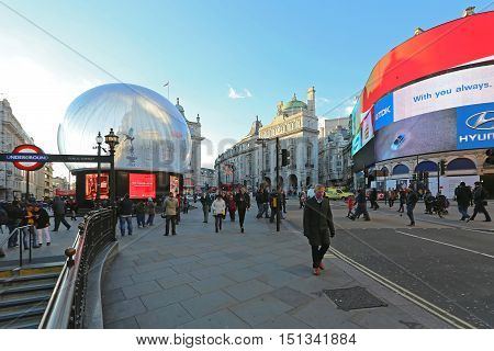 LONDON UNITED KINGDOM - NOVEMBER 19: Christmas at Piccadilly Circus Crowded With People in London on NOVEMBER 19 2013. Big snow globe with Eros Statue at Piccadilly Circus in London United Kingdom.