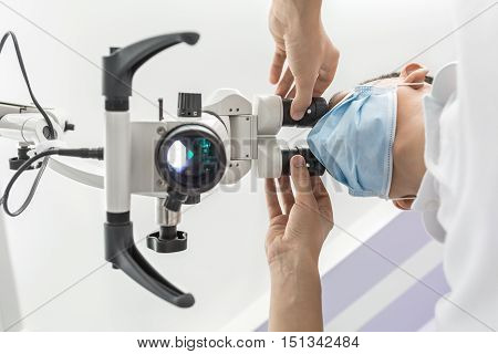 Smart doctor is using the dental microscope in the clinic. He is wearing a white uniform and a blue medical mask. The microscope is glowing. Close-up view from the bottom. Horizontal.