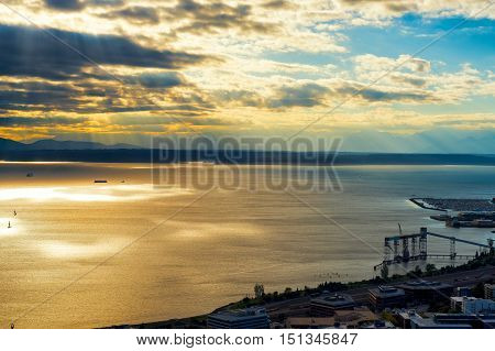 Aerial view of Puget Sound at Seattle lit up by sun rays with Olympic Mountains in the distance