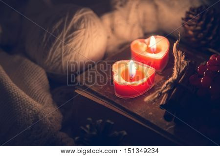 Winter Still Life With A Rowan Berries, Knitted Sweater And A Two Red Candles On A Old Book As A Sym