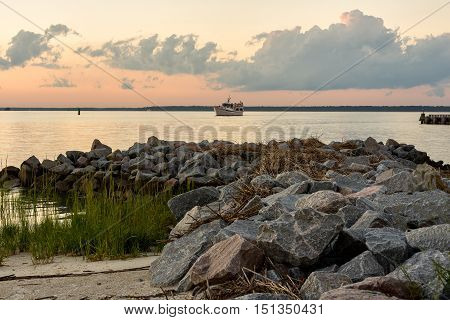 Hilton Head Island at sunset with a boat in the bay with an outcropping of large rocks and beach.
