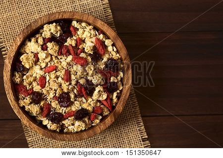 Crunchy oatmeal cereal with almond and dried goji berries and cranberries in wooden bowl photographed overhead on dark wood with natural light (Selective Focus Focus on the top of the cereal)