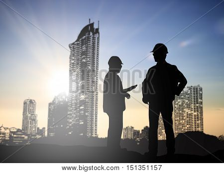 Silhouette Successful male engineer standing survey work on construction over blurred high-voltage pylons and construction. examination inspection survey