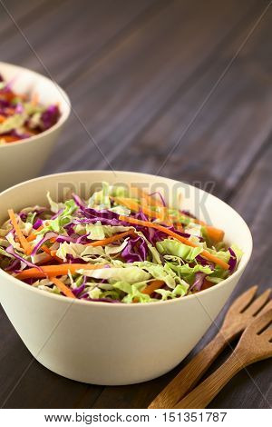 Fresh coleslaw a salad made of shredded red and white cabbage and carrots served in white bowls photographed with natural light (Selective Focus Focus in the middle of the salad)