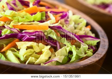 Fresh coleslaw a salad made of shredded red and white cabbage and carrots served in wooden bowl photographed with natural light (Selective Focus Focus one third into the salad)