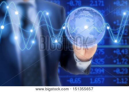 Businessman in a blue suit tapping on a glass globe in front of a stock ticker wall with glowing waves global business concept